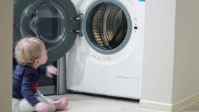 Αγόρι ενός έτους βρεφών αγοράκι που φαίνεται πλυντήριο στο σπίτι Ζητήματα εγχώριων συσκευών απόθεμα βίντεο