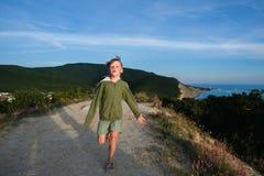 Αγόρι εξάχρονων παιδιών που τρέχει σε έναν δρόμο βουνών στο ηλιοβασίλεμα με την άποψη πόλεων και θάλασσας Δροσερό θερινό βράδυ Στοκ φωτογραφία με δικαίωμα ελεύθερης χρήσης