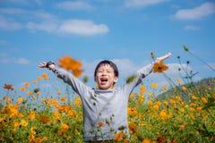 Αγόρι ευτυχές στον τομέα λουλουδιών Στοκ Φωτογραφία