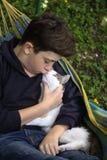 Αγόρι εφήβων με τη γάτα στο NAP hummock Στοκ Εικόνα