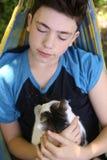 Αγόρι εφήβων με τη γάτα στο NAP hummock Στοκ Φωτογραφία