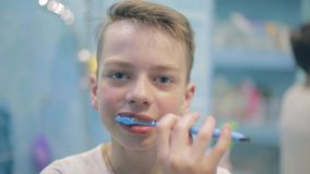 Αγόρι εφήβων που βουρτσίζει τα δόντια του στο λουτρό, υγειονομική περίθαλψη απόθεμα βίντεο