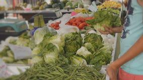 Αγόρι εφήβων που επιλέγει το μαρούλι στην αγροτική αγορά φρούτων και λαχανικών απόθεμα βίντεο