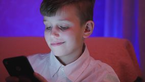 Αγόρι εφήβων που παίζει το τηλεοπτικό παιχνίδι με το smartphone στο εσωτερικό φιλμ μικρού μήκους