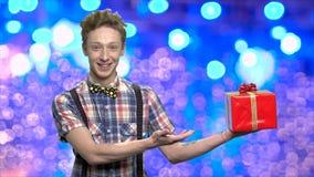 Αγόρι εφήβων που παρουσιάζει κιβώτιο δώρων Χριστουγέννων φιλμ μικρού μήκους