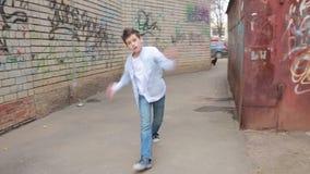 Αγόρι εφήβων που χορεύει, οδός που χορεύει στο υπόβαθρο του τουβλότοιχος απόθεμα βίντεο