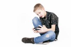 Αγόρι εφήβων που ψάχνει κάτι σε ένα έξυπνο τηλέφωνο που απομονώνεται Στοκ Εικόνες