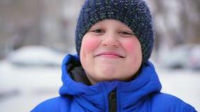 Αγόρι εφήβων σε ένα μπλε κάτω από το γέλιο σακακιών Χειμώνας, μειωμένο χιόνι απόθεμα βίντεο
