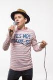 Αγόρι εφήβων brunette τραγουδιστών σε ένα ρόδινο Τζέρσεϋ στο χρυσό καπέλο με ένα μικρόφωνο Στοκ εικόνα με δικαίωμα ελεύθερης χρήσης