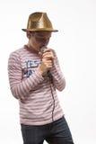 Αγόρι εφήβων brunette τραγουδιστών σε ένα ρόδινο Τζέρσεϋ στο χρυσό καπέλο με ένα μικρόφωνο Στοκ Εικόνα
