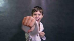 Αγόρι εφηβικό karate κιμονό στον κυματισμό χεριών πάλης απόθεμα βίντεο