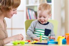 Αγόρι και γυναίκα παιδιών παιδιών που παίζουν το ζωηρόχρωμο παιχνίδι αργίλου στο βρεφικό σταθμό ή τον παιδικό σταθμό Στοκ φωτογραφία με δικαίωμα ελεύθερης χρήσης