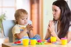 Αγόρι και γυναίκα παιδιών που παίζουν το ζωηρόχρωμο παιχνίδι αργίλου Στοκ φωτογραφία με δικαίωμα ελεύθερης χρήσης