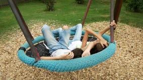Αγόρι και κορίτσι, δίδυμα που ταλαντεύονται σε μια ταλάντευση μια αιώρα στο λούνα παρκ στην πόλη 4k, διάστημα αντιγράφων απόθεμα βίντεο
