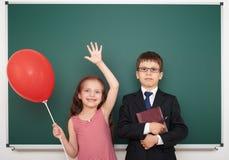 Αγόρι και κορίτσι κοντά στο σχολικό πίνακα Στοκ Εικόνα