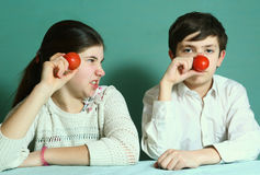 Αγόρι και κορίτσι με τη στενή επάνω φωτογραφία μύτης ντοματών Στοκ εικόνα με δικαίωμα ελεύθερης χρήσης