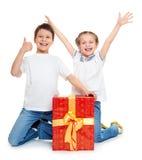 Αγόρι και κορίτσι με το κόκκινο κιβώτιο δώρων και το χρυσό τόξο - έννοια αντικειμένου διακοπών που απομονώνεται Στοκ Εικόνες