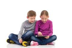 Αγόρι και κορίτσι που απολαμβάνουν τη νέα ταμπλέτα Στοκ φωτογραφία με δικαίωμα ελεύθερης χρήσης