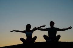 Αγόρι και κορίτσι που κυματίζουν τα χέρια τους στο ηλιοβασίλεμα Στοκ Εικόνα