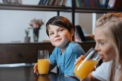 Αγόρι και κορίτσι που πίνουν το χυμό από πορτοκάλι στην κουζίνα από κοινού Στοκ Φωτογραφίες