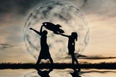 Αγόρι και κορίτσι σκιαγραφιών που κρατούν ένα έγγραφο πυραύλων Στοκ Φωτογραφία