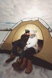 Αγόρι και κορίτσι στα χειμερινά ενδύματα που κάθονται σε μια σκηνή Στοκ εικόνα με δικαίωμα ελεύθερης χρήσης