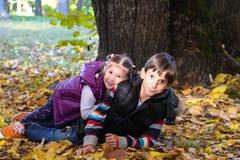 Αγόρι και κορίτσι στην ηλιόλουστη συνεδρίαση πάρκων φθινοπώρου στα φύλλα Στοκ φωτογραφία με δικαίωμα ελεύθερης χρήσης
