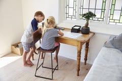 Αγόρι και κορίτσι στην κρεβατοκάμαρα με την ψηφιακή ταμπλέτα που κάνει την εργασία Στοκ φωτογραφία με δικαίωμα ελεύθερης χρήσης