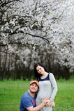 Αγόρι και κορίτσι στο υπόβαθρο του ανθίζοντας βερίκοκου Ένας τύπος αγκαλιάζει Στοκ Φωτογραφίες