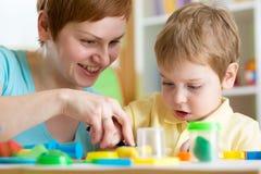 Αγόρι και μητέρα παιδιών που παίζουν το ζωηρόχρωμο παιχνίδι αργίλου Στοκ φωτογραφία με δικαίωμα ελεύθερης χρήσης