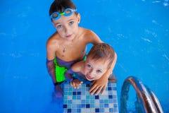 Αγόρι και ο χαριτωμένος χαμογελώντας αδελφός μωρών του μετά από το ντους στην πισίνα Στοκ Φωτογραφίες