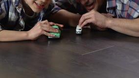 Αγόρι και πατέρας που ανταγωνίζονται στα αυτοκίνητα παιχνιδιών που συναγωνίζονται στο πάτωμα στο σπίτι, που παίζει το παιχνίδι απόθεμα βίντεο