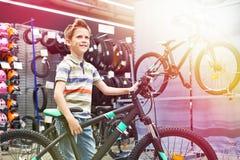 Αγόρι και ποδήλατο στο αθλητικό κατάστημα στοκ εικόνα