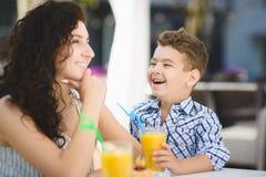 Αγόρι και το δοκιμάζοντας επιδόρπιο μητέρων του με το χυμό στο εστιατόριο θερέτρου υπαίθριο Στοκ φωτογραφία με δικαίωμα ελεύθερης χρήσης