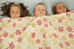 Αγόρι και δύο κορίτσια κοιμισμένα κάτω από ένα κάλυμμα στοκ φωτογραφία