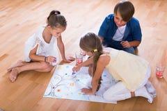 Αγόρι και δύο κορίτσια που παίζουν στο επιτραπέζιο παιχνίδι στο εσωτερικό στοκ φωτογραφίες