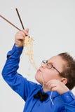 αγόρι κινέζικα που τρώει τα πεινασμένα noodles ραβδιά Στοκ εικόνες με δικαίωμα ελεύθερης χρήσης