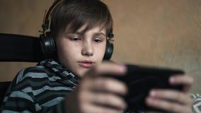 Αγόρι κινηματογραφήσεων σε πρώτο πλάνο που ακούει τη μουσική στα ακουστικά  απόθεμα βίντεο