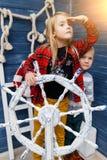 Αγόρι, κορίτσι στο τιμόνι θάλασσας Στοκ Φωτογραφίες