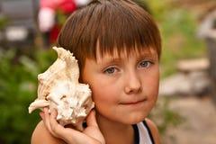 Αγόρι με ένα κοχύλι Στοκ Φωτογραφία