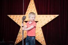 Αγόρι με ένα μικρόφωνο στη λαϊκή σκηνή Στοκ Εικόνες