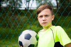 Αγόρι με ένα παίζοντας ποδόσφαιρο σφαιρών Στοκ Φωτογραφία