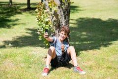 Αγόρι με κινητό στον κήπο Στοκ Εικόνα