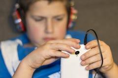 Αγόρι με τα ακουστικά και το κινητό τηλέφωνο υπό εξέταση Στοκ φωτογραφία με δικαίωμα ελεύθερης χρήσης