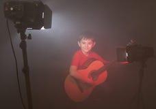 Αγόρι με την ακουστική κιθάρα στην ομίχλη Στοκ Εικόνες