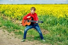 Αγόρι με την ακουστική κιθάρα υπαίθρια στοκ φωτογραφίες