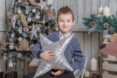 Αγόρι με την ασημένια συνεδρίαση αστεριών στο έλκηθρο κάτω από το χριστουγεννιάτικο δέντρο στοκ εικόνες με δικαίωμα ελεύθερης χρήσης