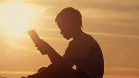 Αγόρι με την ταμπλέτα στη συνεδρίαση ηλιοβασιλέματος στο βουνό Στοκ εικόνες με δικαίωμα ελεύθερης χρήσης