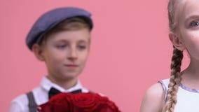 Αγόρι με τη δέσμη των λουλουδιών που στέκονται πίσω από το κορίτσι, που προετοιμάζεται να κάνει την έκπληξη, ημερομηνία φιλμ μικρού μήκους