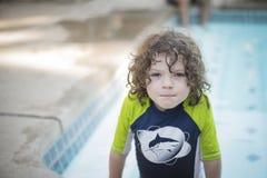 Αγόρι με τη σγουρή τρίχα στην πισίνα στοκ εικόνες